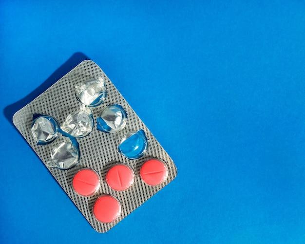 医薬品の準備は、青色の背景に錠剤でブリスターを開きます。