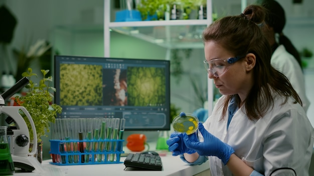 Pharmaceutical researcher analyzing solution test from petri dish
