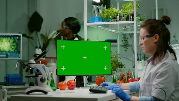 녹색 화면 크로마 키를 조롱하는 컴퓨터를 보고 있는 제약 연구원