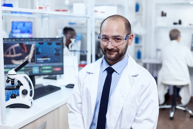 Фармацевтический исследователь сидит на стуле, глядя на камеру. серьезный эксперт по генетике в лаборатории с современными технологиями для медицинских исследований с африканским помощником на заднем плане.