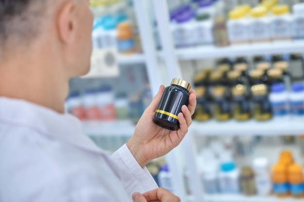 Pharmaceutist looking at a dietary supplement in his hand