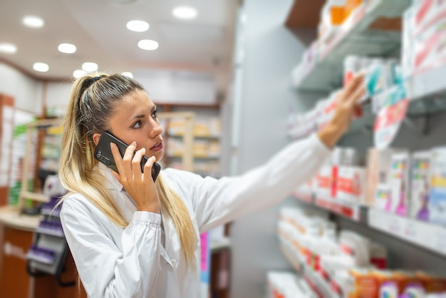 Pharmacist checking drug in a pharmacy while talking on the phone