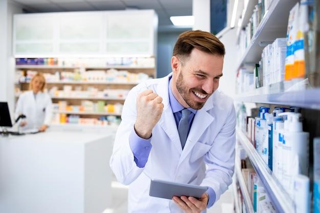 Фармацевт проверяет инвентарь медикаментов на планшетном компьютере в аптеке.