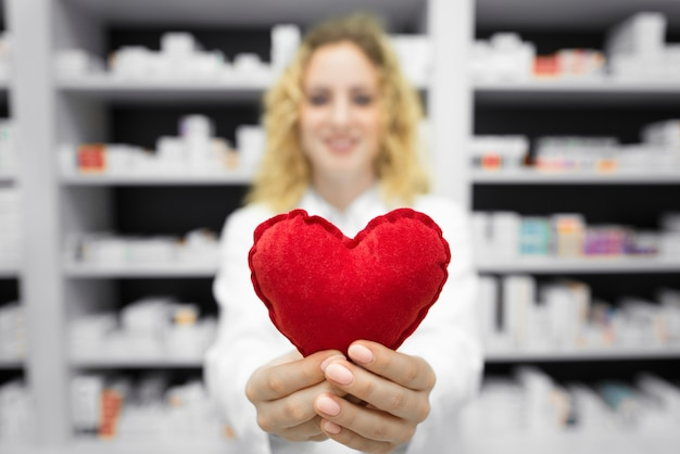 Pharmacist in drug store holding heart