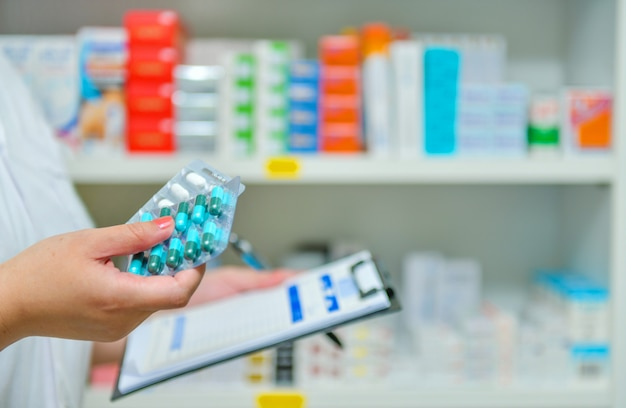 Pharmacist filling prescription in blur pharmacy drugstore