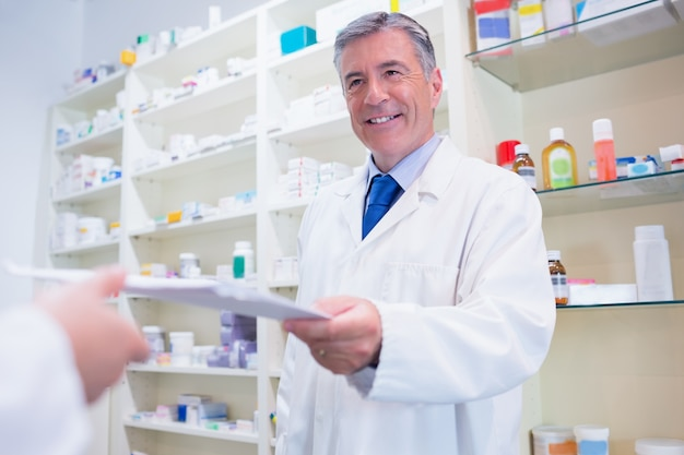 Pharmacist handing a prescription to somebody