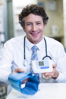 薬剤師が薬局で血圧モニターを保持