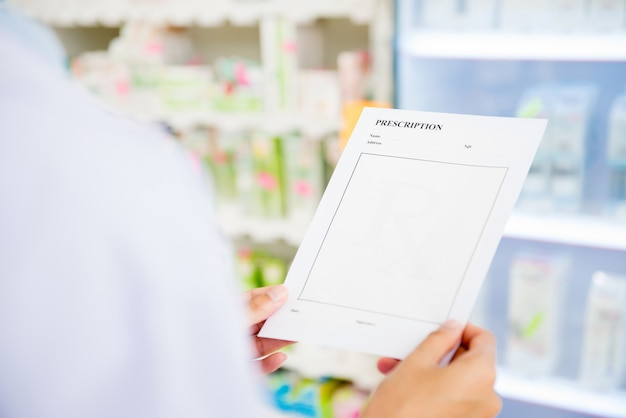 Pharmacist holding and looking at rx prescription in chemist shop or pharmacy