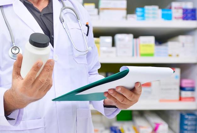 薬局のドラッグストアで処方箋を記入するための薬瓶とコンピューターのタブレットを保持している薬剤師