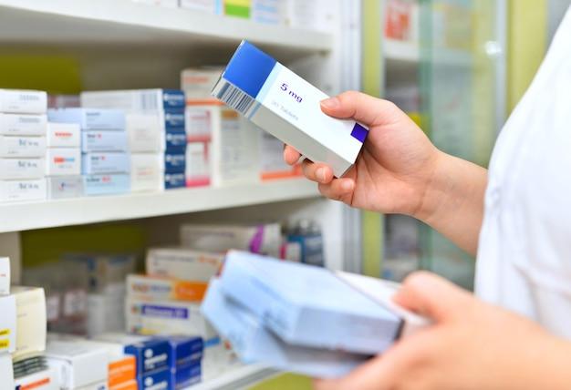 Pharmacist holding medicine box in pharmacydrugstore