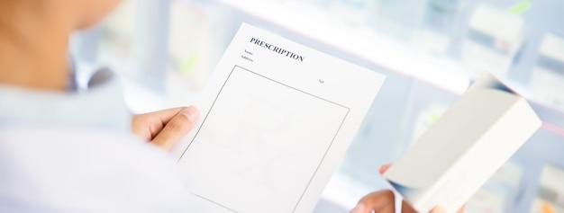 Pharmacist holding prescription checking medicine in pharmacy
