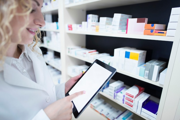 Pharmacist holding tablet by the shelf full of medicine in drug store and checking medication availability and specification