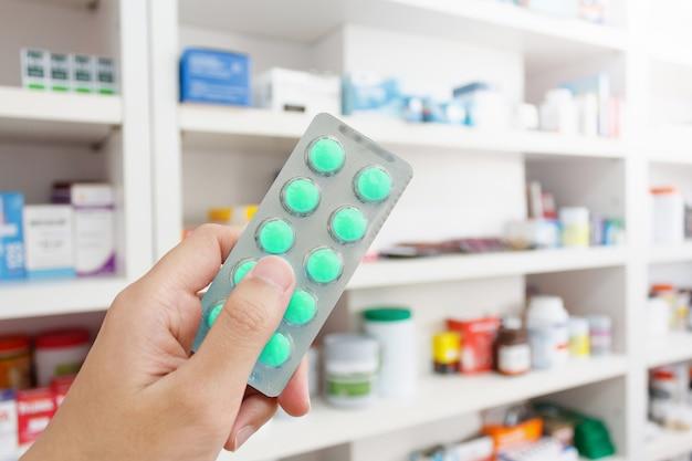 Фармацевт держит таблетки в аптеке