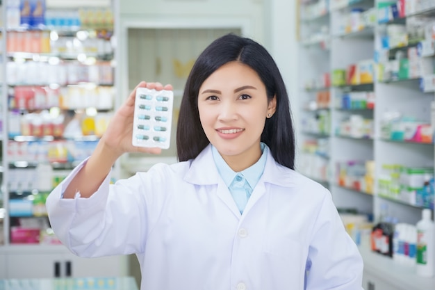 Pharmacist holds a packet of pills in her hands.