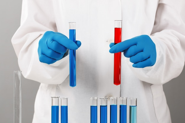 Pharmacist holds test tubes with red and blue liquids