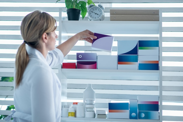 Фармацевт в лабораторном халате кладет лекарство на полку