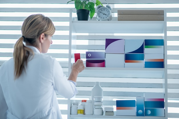 Фармацевт в лабораторном халате принимает лекарство с полки