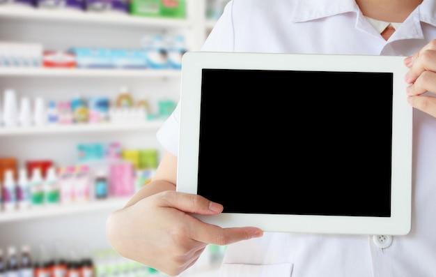 Фармацевт в белом халате показывает пустой цифровой планшетный компьютер с полками лекарств в аптеке