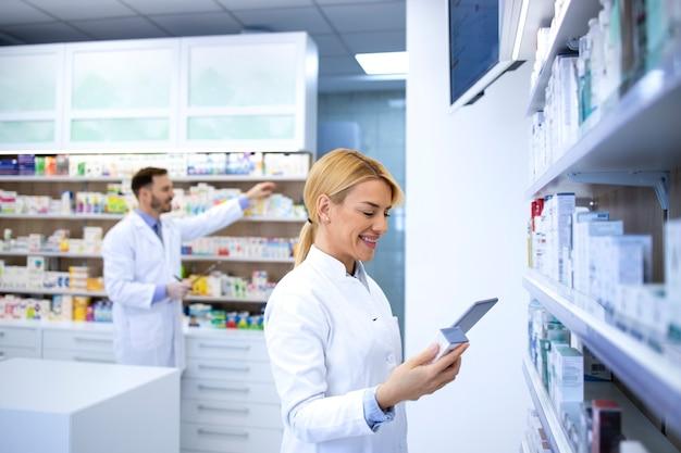 Аптекарь в белых халатах работает в аптеке и готовит лекарства для продажи.