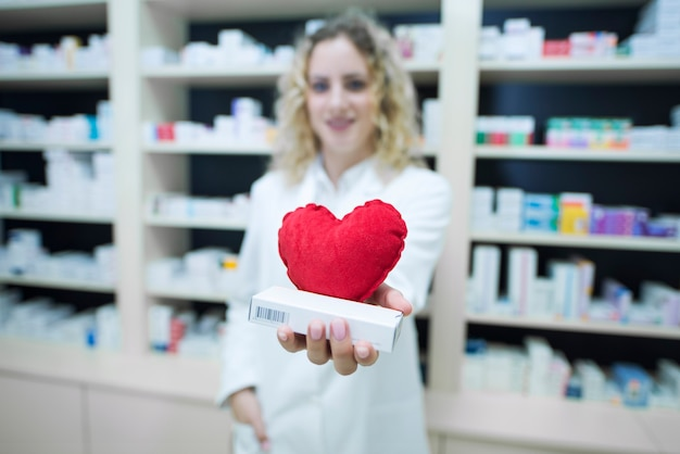 Фармацевт в белой форме держит лекарства от сердечно-сосудистых заболеваний