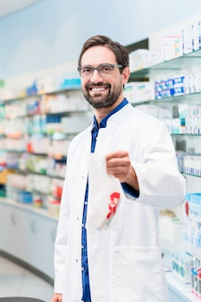 Pharmacist in pharmacy selling pharmaceuticals in bag