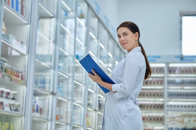 Pharmacist posing for the camera among shelves with healthcare products