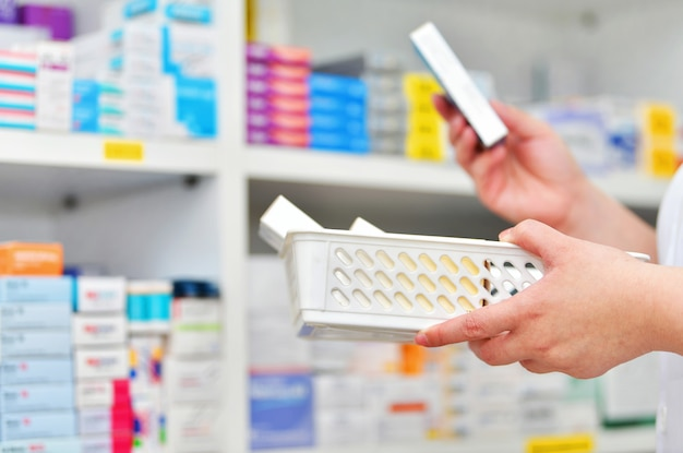 Pharmacist refills the shelves with new stocks in pharmacy drugstore