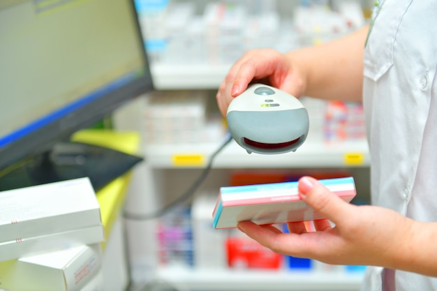 Pharmacist scanning barcode of medicine drug in a pharmacydrugstore