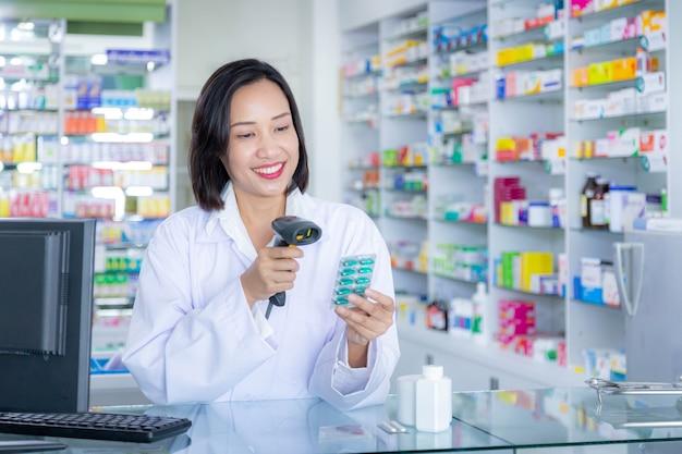 薬剤師が薬局のドラッグストアで医薬品のバーコードをスキャンします。ヘルスケアと医療の概念。
