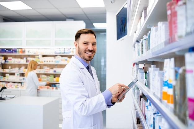 薬剤師が薬を持って棚のそばに立ち、ドラッグストアでタブレットに入力します。