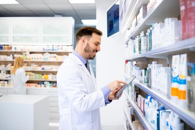 薬剤師が薬を持って棚のそばに立ち、薬局でタブレットに入力します。