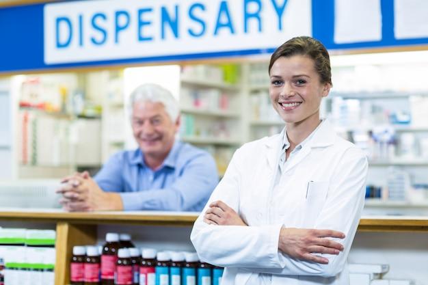 Фармацевт, стоя со скрещенными руками в аптеке