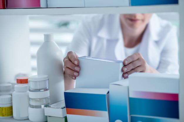 Фармацевт берет лекарство с полки в аптеке