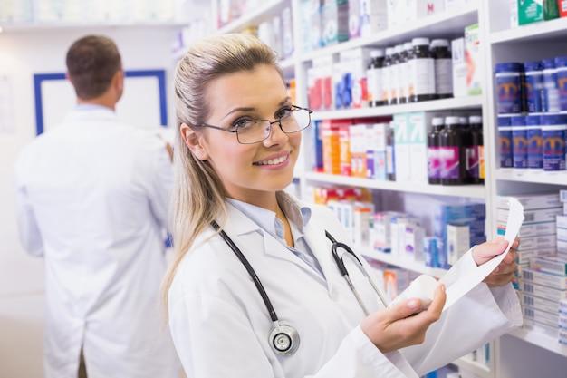 Фармацевт, принимающий лекарство с полки