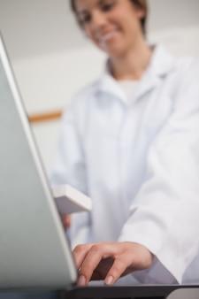 Фармацевт, печатающий на ноутбуке
