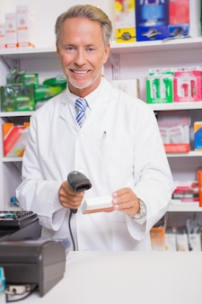 Pharmacist using machine and holding medicine