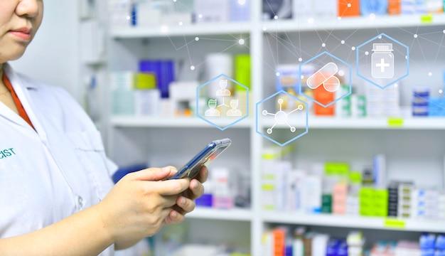 Pharmacist using mobile smart phone for search bar on display in pharmacy drugstore shelves