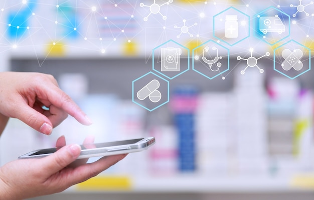 Pharmacist using mobile smart phone for search bar on display in pharmacy drugstore