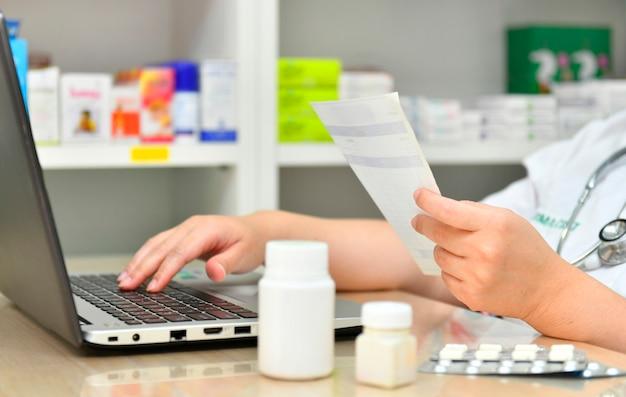 Фармацевт, используя ноутбук в аптеке