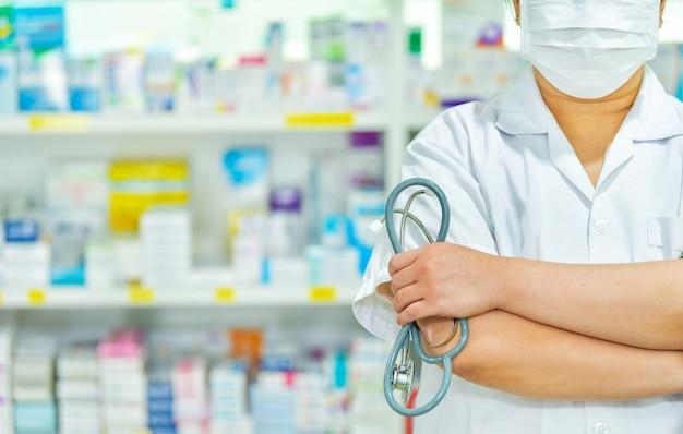 薬剤師はフェイスマスクを着用し、薬局のドラッグストアで聴診器を保持しています。コピースペース