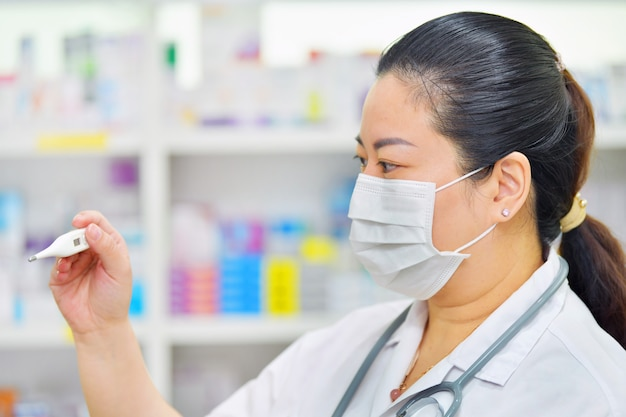 Pharmacist wearing n95 mask with thermometer and stethoscope on many medicine shelf background. coronavirus (covid-19)concept of disease, flu treatment and protection