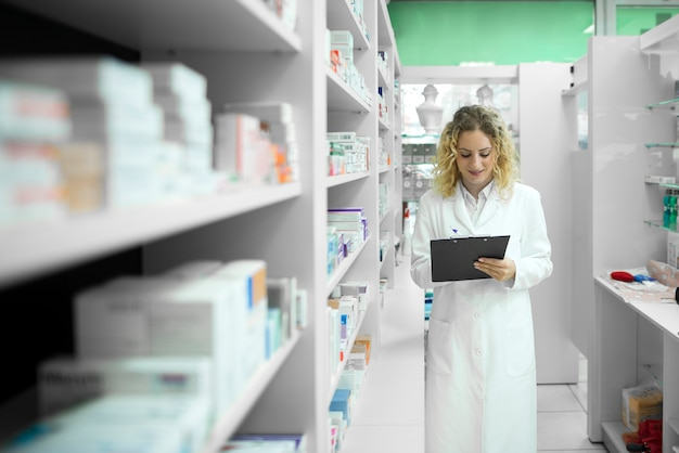 Pharmacist in white uniform walking by the shelf with medicines and checking inventory