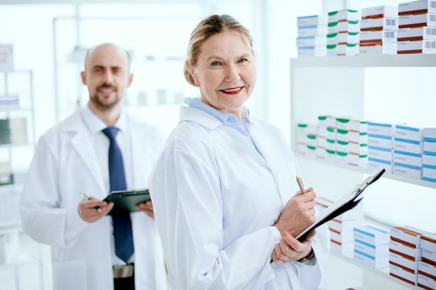 클립보드가 있는 약사와 약국 진열장 근처에 서 있는 동료