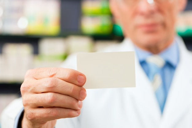 Pharmacist with business card in pharmacy
