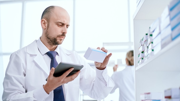 Pharmacist with a digital tablet looking at a box of medicines