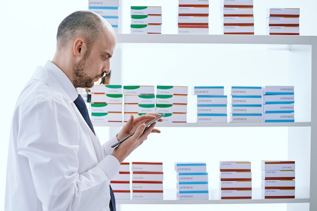 Pharmacist with a digital tablet standing near a medicine showcase