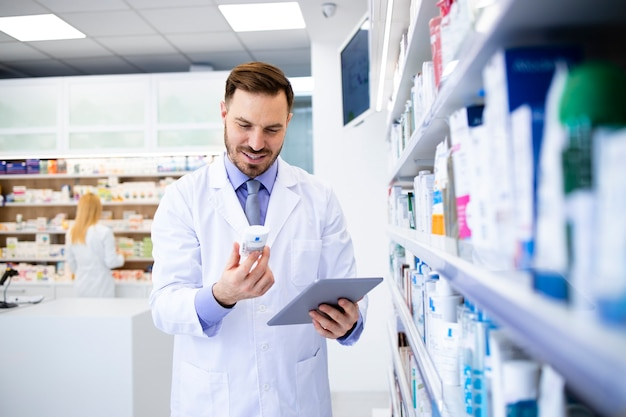 Pharmacist working in drug store and checking medicine expiration date on tablet computer.