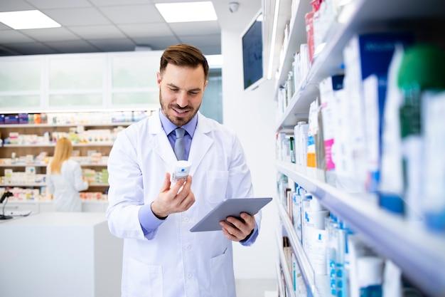 ドラッグストアで働いており、タブレットコンピューターで薬の有効期限を確認している薬剤師。