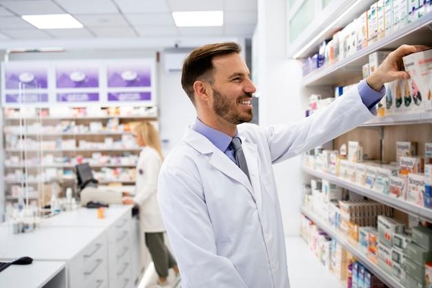 薬局で働いている薬剤師が棚に薬の箱を並べています。