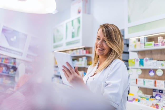 Pharmacist working with a tablet in the pharmacy holding it in her hand while reading info